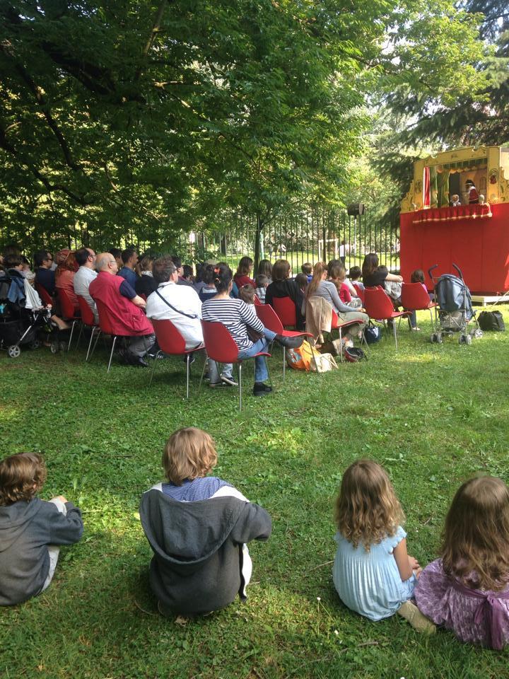 Bambini ed adulti assistono alla spettacolo al giardino delle Triennale di Milano